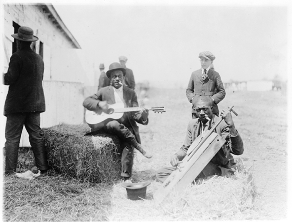 Black musicians playing for tips by a stable - Courtesy Library of Congress They are both playing kazoos, often a lead instrument in jug bands. Jug bands included string instruments and <br /> often someone blowing across the top of a jug for a bass line.